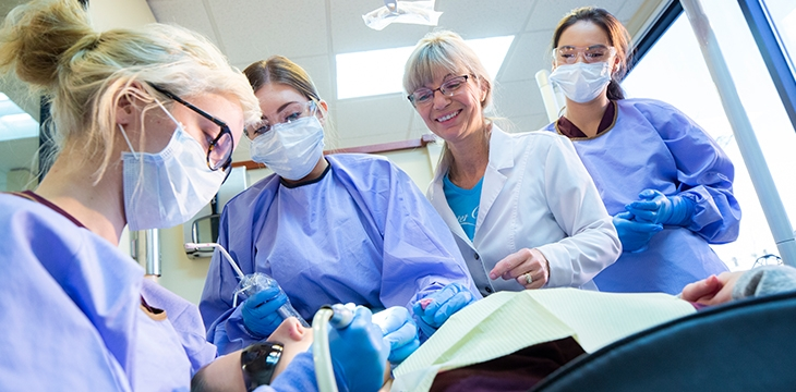 group of dental students working on patient